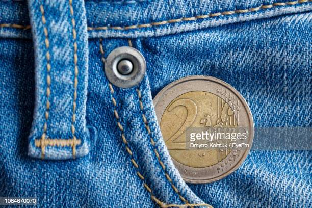 close-up of coin in jeans pocket - silver trousers stock pictures, royalty-free photos & images