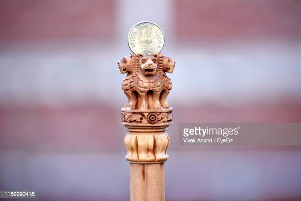 close-up of coin on wooden lion statues - economy stock pictures, royalty-free photos & images