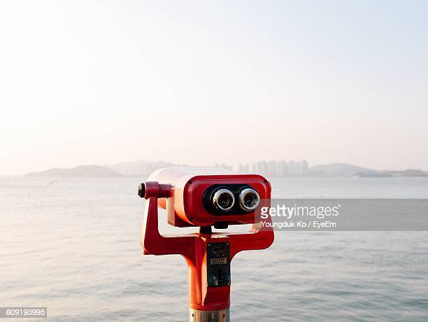 close-up of coin operated binoculars facing sea - binoculars stock pictures, royalty-free photos & images