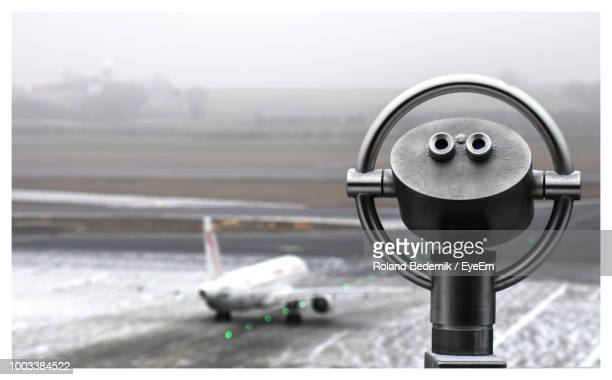 Close-Up Of Coin-Operated Binoculars Against Airport Runway