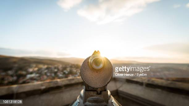 close-up of coin-operated binoculars against cityscape during sunset - binoculars stock pictures, royalty-free photos & images