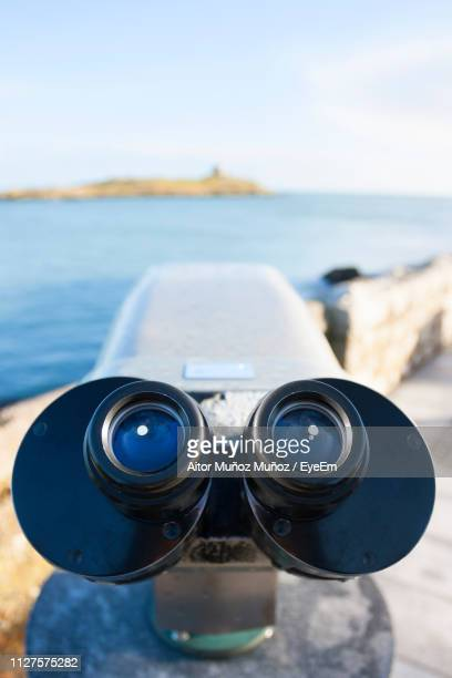 close-up of coin-operated binoculars at beach against sky - dalkey stock pictures, royalty-free photos & images