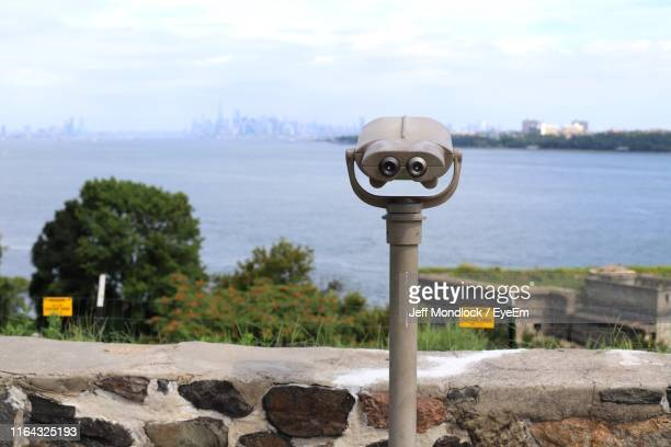 close-up of coin-operated binoculars by retaining wall - staten island stock pictures, royalty-free photos & images