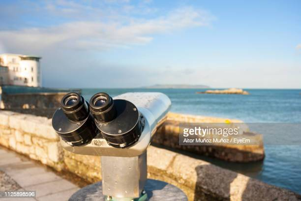 close-up of coin-operated binoculars by sea against sky - dalkey stock pictures, royalty-free photos & images