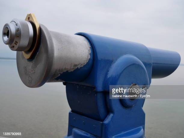 close-up of coin-operated binoculars by sea against sky - sabine hauswirth stock pictures, royalty-free photos & images