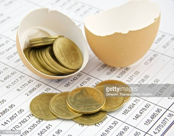 close-up of coins and eggshells on paper - eggshell stock pictures, royalty-free photos & images