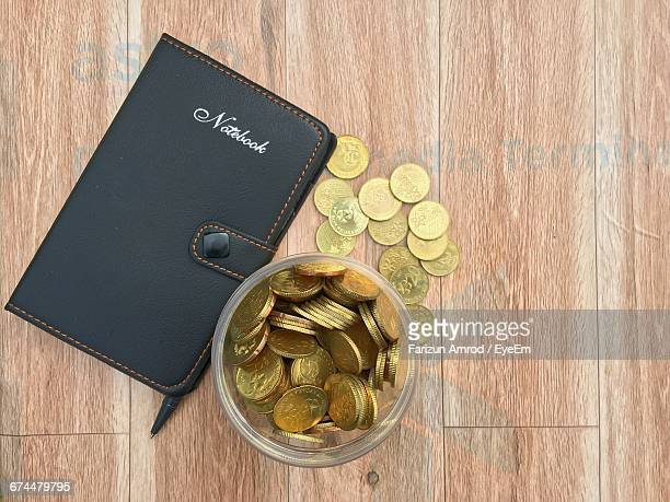 close-up of coins and notebook on wooden table - malaysian ringgit stock photos and pictures