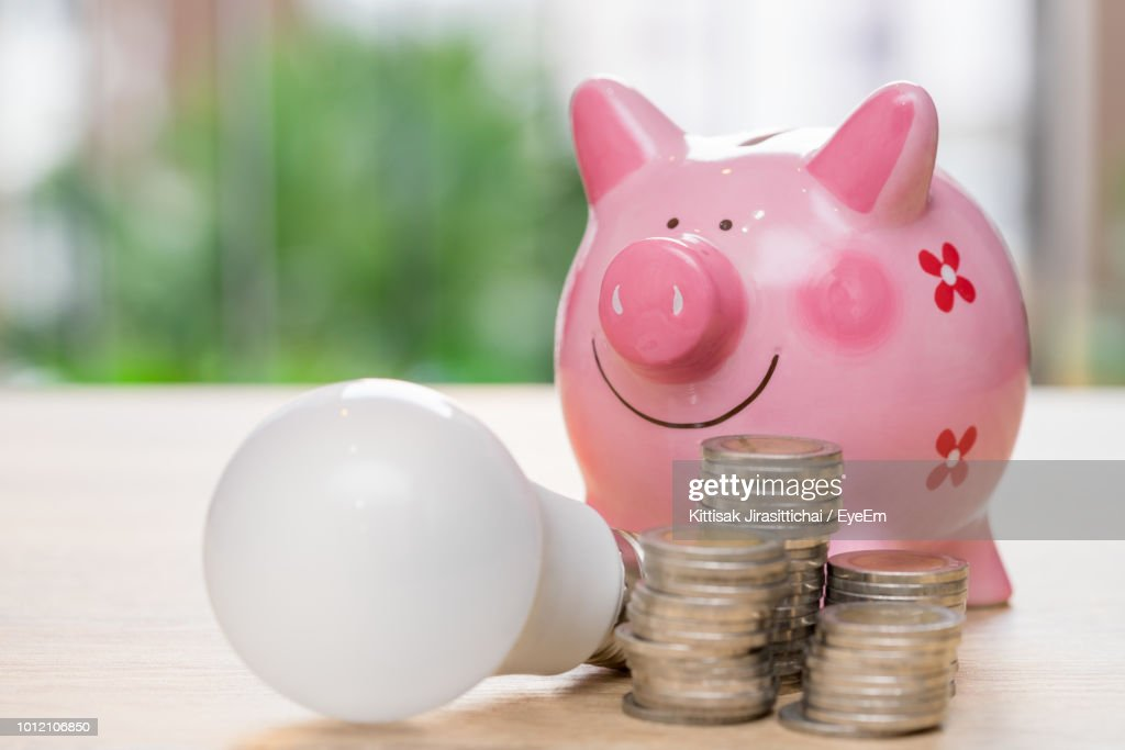 Close Up Of Coins By Light Bulb And Piggy Bank On Table Stock Photo