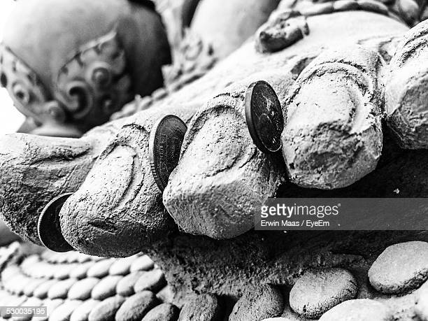 close-up of coins in between statue leg - between stock pictures, royalty-free photos & images
