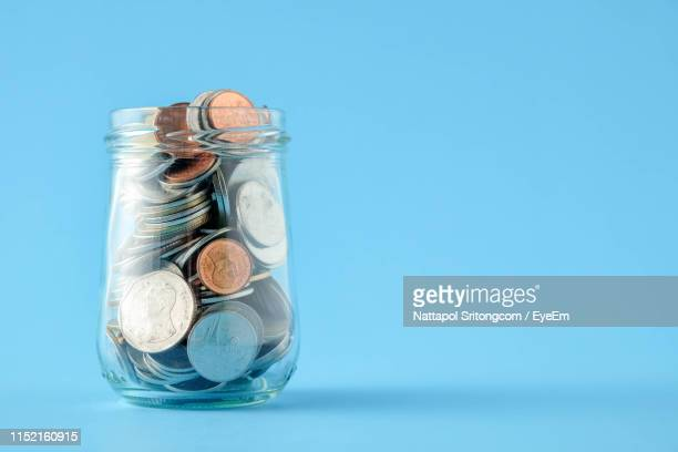 close-up of coins in glass jar on blue background - jar stock pictures, royalty-free photos & images