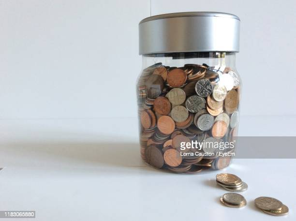 close-up of coins in jar on table - saving stock pictures, royalty-free photos & images