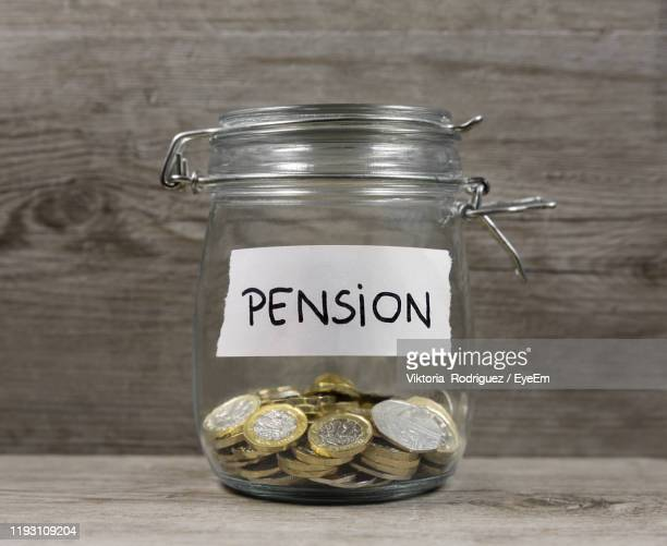 close-up of coins in jar on table - retirement stock pictures, royalty-free photos & images
