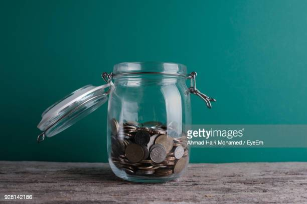 close-up of coins in jar on table - jar stock pictures, royalty-free photos & images