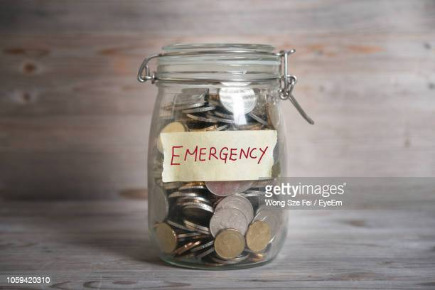 close-up of coins in jar with emergency text on table - accidents and disasters stock pictures, royalty-free photos & images