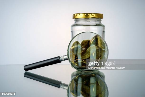 Close-Up Of Coins In Jar With Magnifying Glass On Table