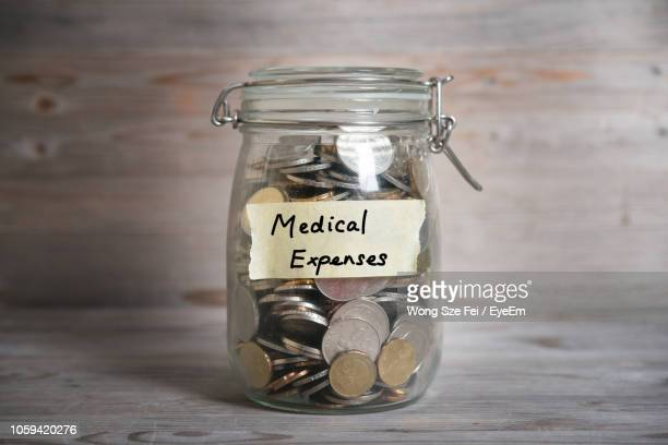 close-up of coins in jar with text on table - westers schrift stockfoto's en -beelden