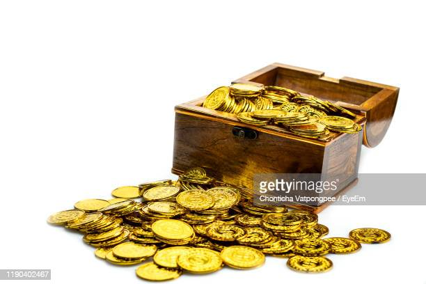 close-up of coins in wooden chest on white background - 宝箱 ストックフォトと画像