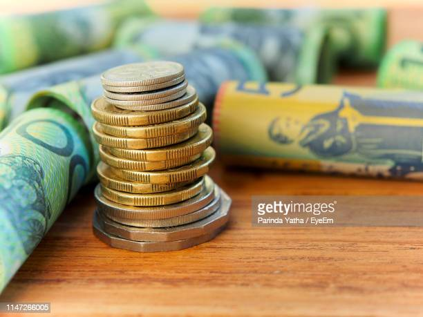 close-up of coins stack by paper currency on table - finance and economy stock pictures, royalty-free photos & images