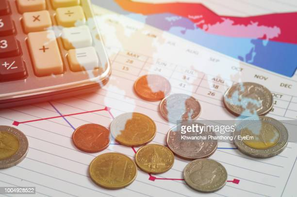 Close-Up Of Coins With Calculator And Pen On Table