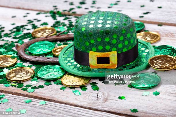 close-up of coins with horseshoe and hat on wooden table - st patricks day stock pictures, royalty-free photos & images
