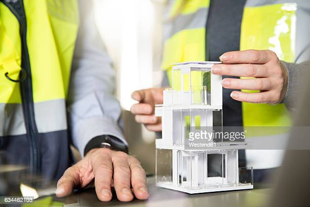 Close-up of colleagues wearing reflective vests with architectural model