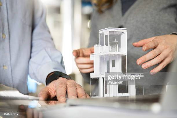 Close-up of colleagues with architectural model