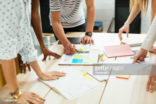 close-up of colleagues working together at desk in office discussing papers - brainstorming stock pictures, royalty-free photos & images