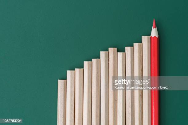 close-up of colored pencil by normal pencils against green 0background - bar graph stock pictures, royalty-free photos & images