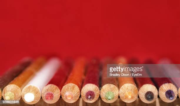 Close-Up Of Colored Pencils Against Red Background