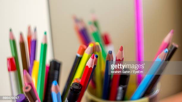 Close-Up Of Colored Pencils Against Wall