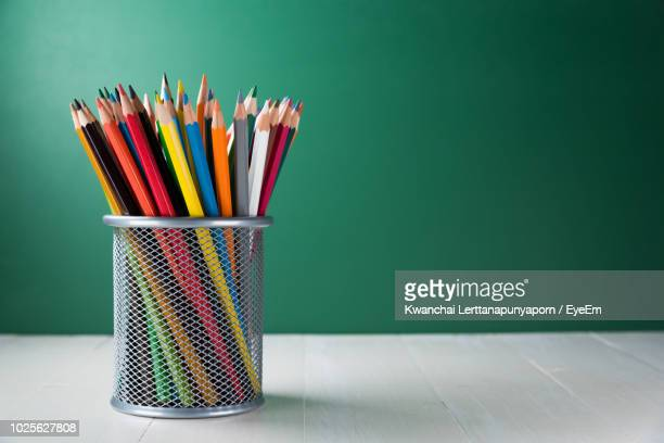 close-up of colored pencils in container against wall - pencil case stock pictures, royalty-free photos & images