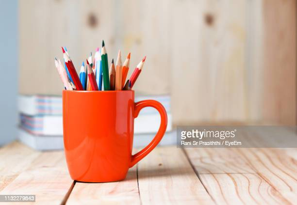 close-up of colored pencils in cup on table - arti e mestieri foto e immagini stock