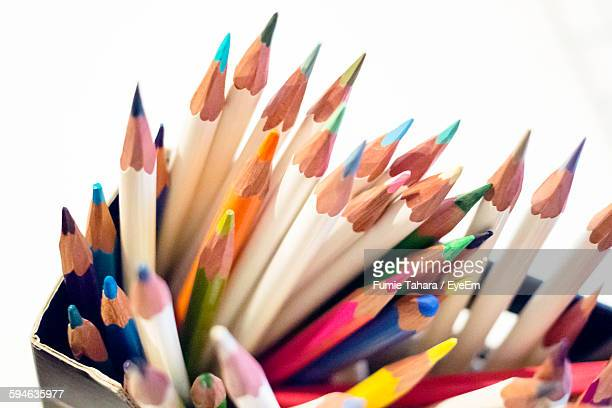 Close-Up Of Colored Pencils On Container Against White Background