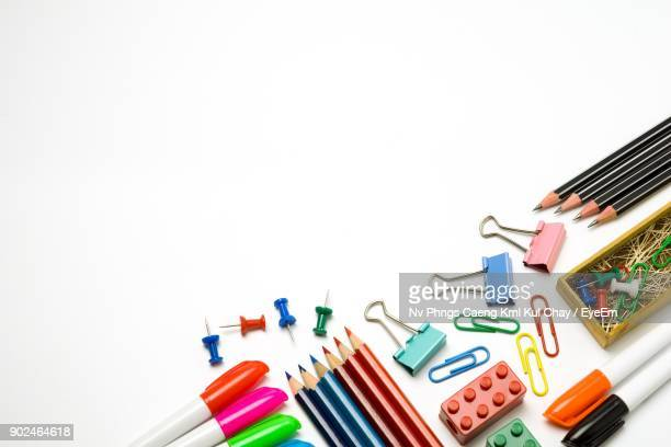 close-up of colored pencils with school supplies on white background - schulbedarf stock-fotos und bilder