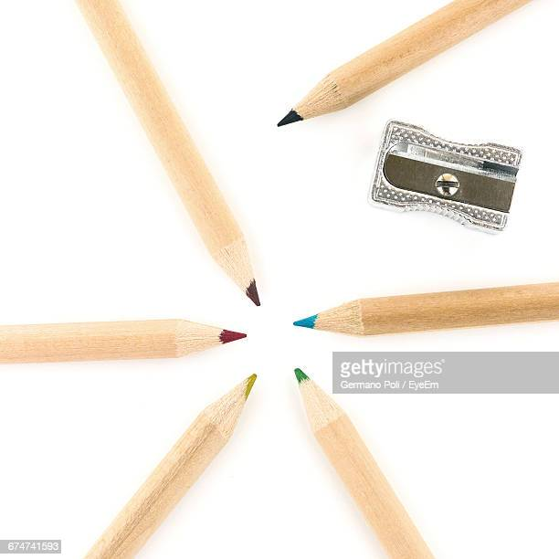 Close-Up Of Colored Pencils With Sharpener On White Background