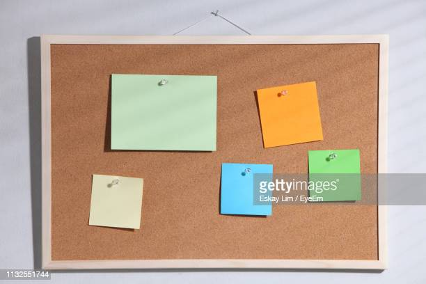 close-up of colorful adhesive notes on bulletin board - bulletin board stock pictures, royalty-free photos & images