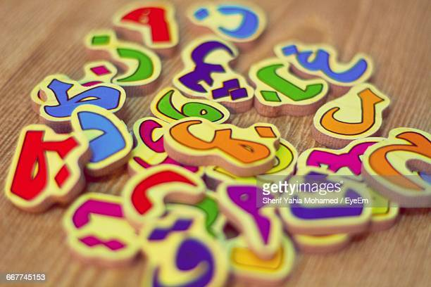 Close-Up Of Colorful Arabic Letters On Wooden Table