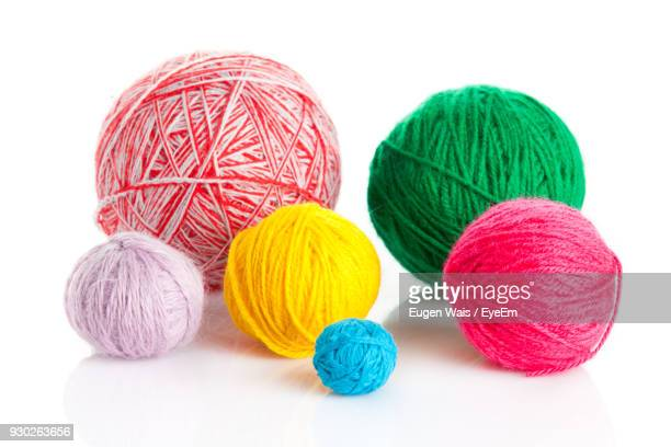 Close-Up Of Colorful Ball Of Wools Against White Background