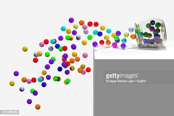 Close-Up Of Colorful Balls Falling From Jar Against White Background