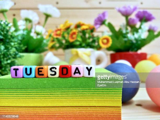 close-up of colorful blocks with tuesday text on stacked papers over table - tuesday stock photos and pictures
