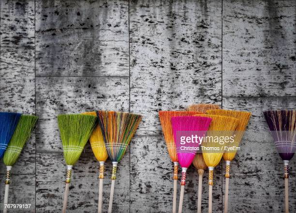 Close-Up Of Colorful Brooms Against Wall