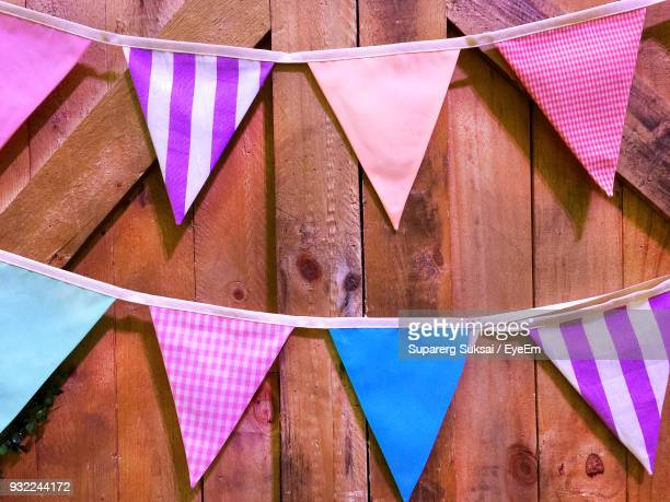 close-up of colorful buntings hanging on wooden fence - banderines fotografías e imágenes de stock