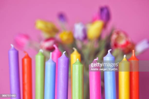 Close-Up Of Colorful Candles Against Colored Background