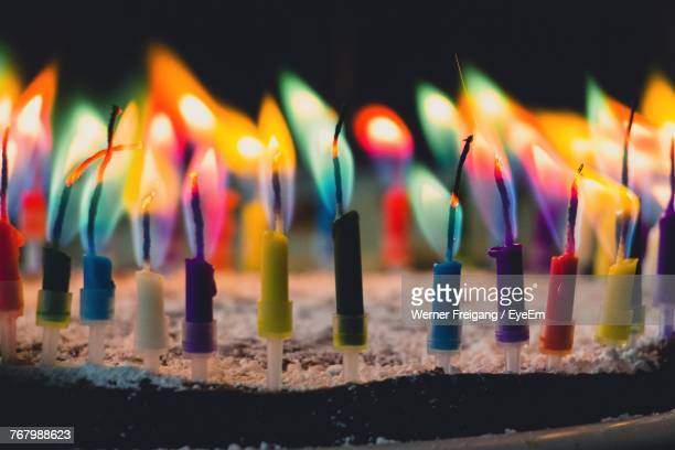 close-up of colorful candles burning on birthday cake - birthday cake stock photos and pictures