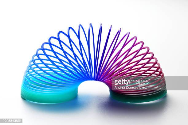 close-up of colorful coiled spring toy against white background - flexibility stock pictures, royalty-free photos & images