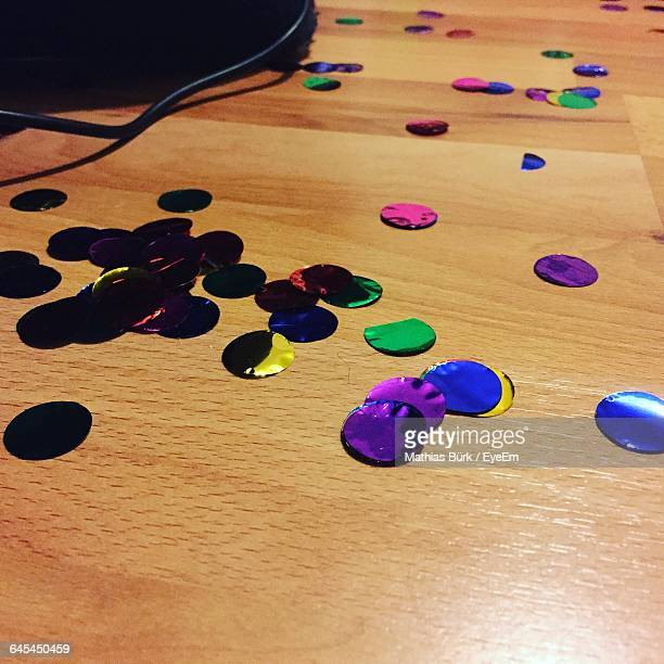 Close-Up Of Colorful Confetti Fallen On Hardwood Floor