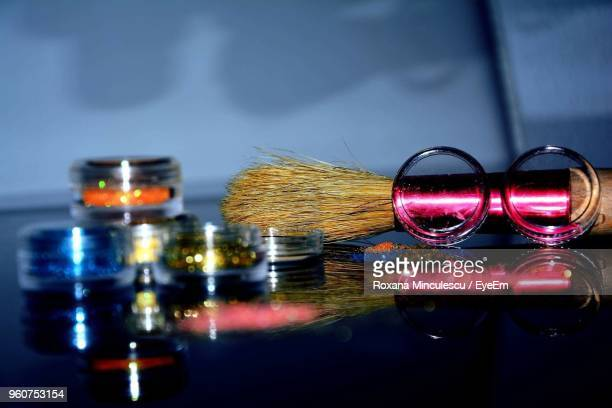 Close-Up Of Colorful Containers By Shaving Brush On Table