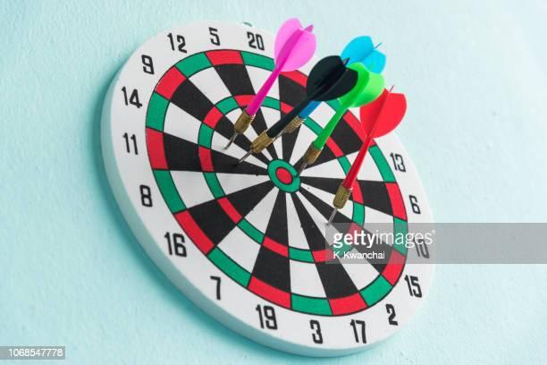close-up of colorful darts on dartboard - darts stock-fotos und bilder