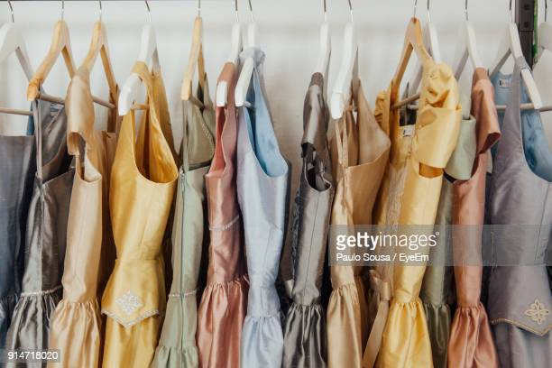 close-up of colorful dress hanging on display at store - evening gown stock photos and pictures