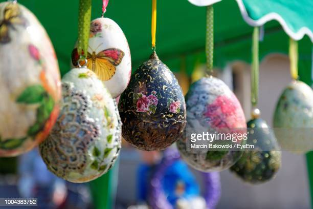 close-up of colorful easter eggs hanging at market - happy easter text stock pictures, royalty-free photos & images
